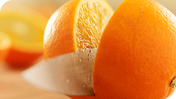 Fresh orange being sliced in half with a knife