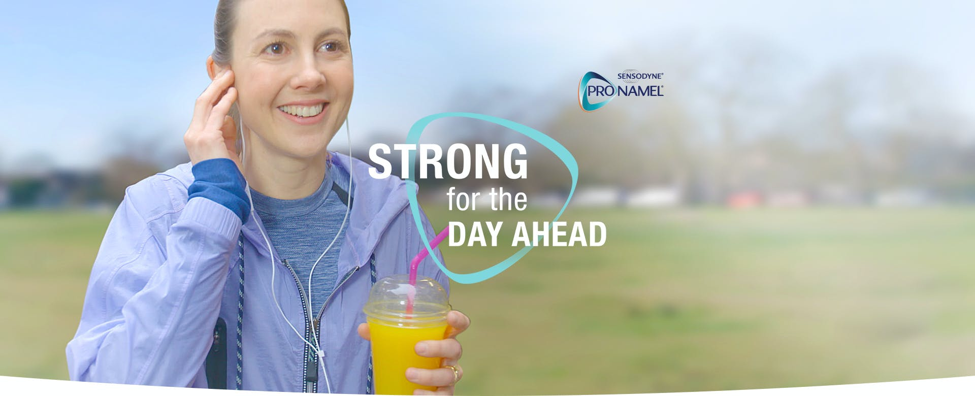 Smiling girl in jogging attire with earphones and drink