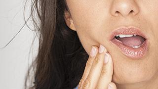 dientes sensibles - mujer sufriendo por la sensibilidad dental - sensodyne