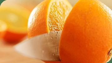 Knife cutting an orange