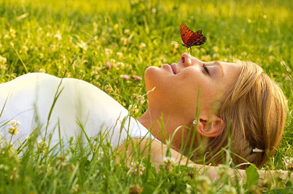 Woman lying in a grass field with a butterfly sitting on her nose