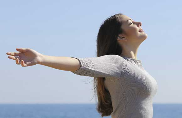 Woman with outstretched arms breathing in the air