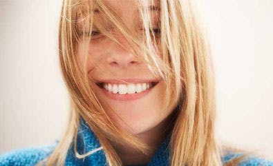 Young blonde woman smiling with closed eyes