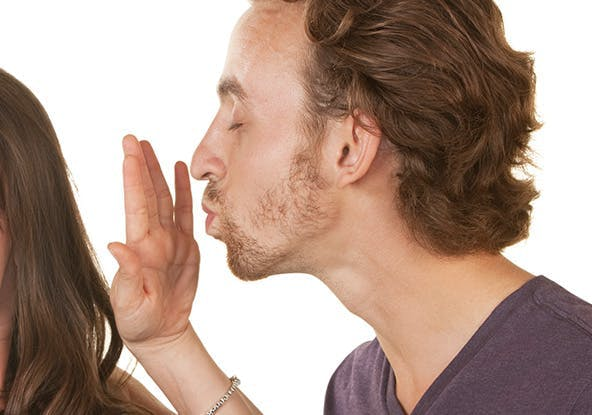 Man trying to kiss a woman but she stops him with her hand