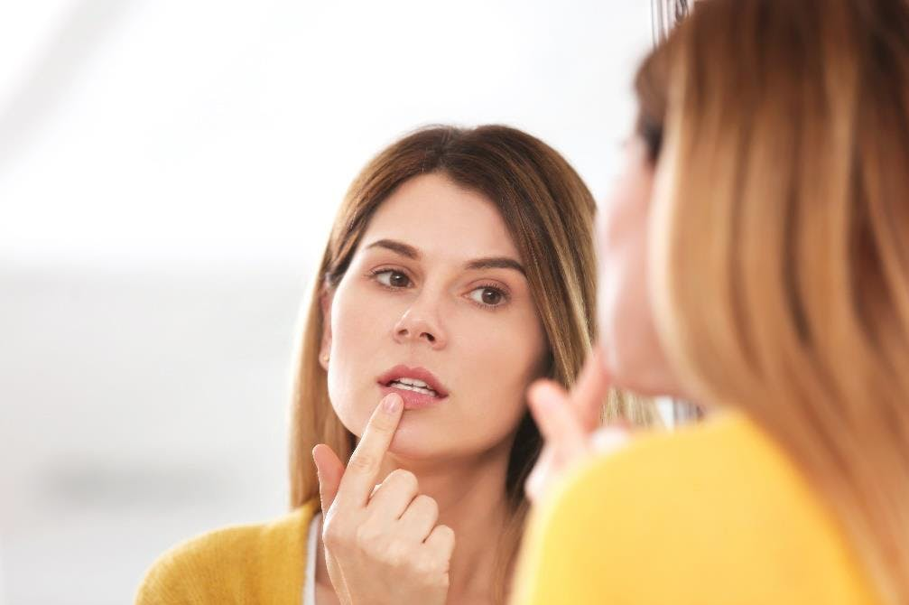 Women looking into a mirror touching her lip