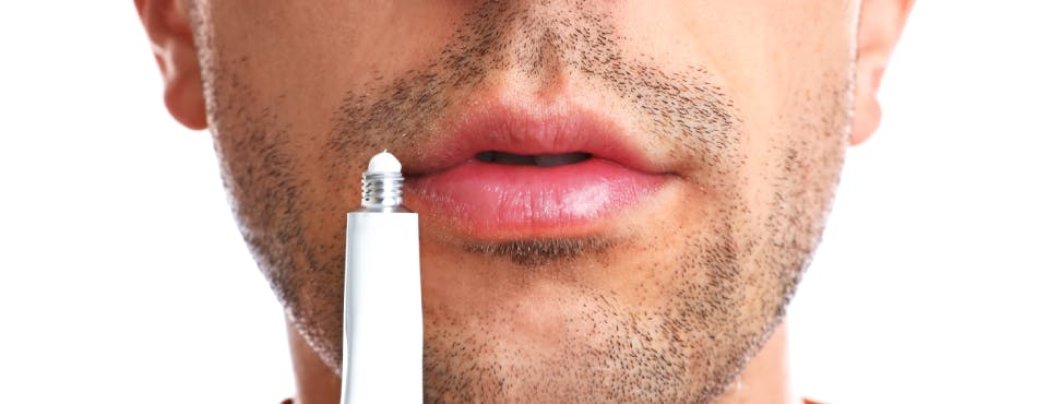 Man preparing to use cold sore ointment
