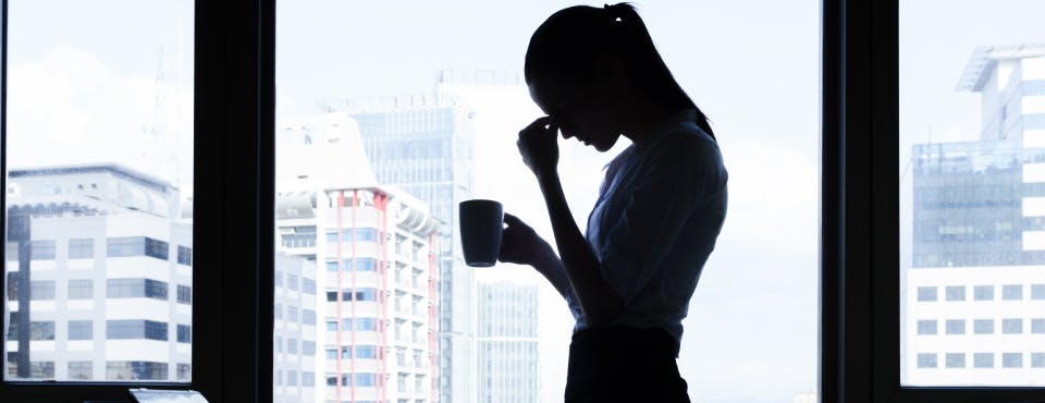 Silhouette of stressed business woman in high-rise building