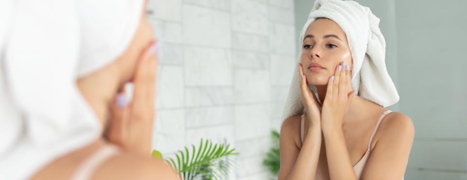 Woman looking at face in bathroom mirror
