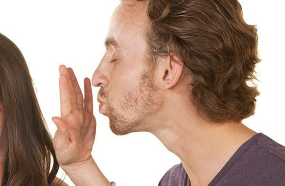 Un homme qui s'apprête à embrasser une femme qui l'arrête de la main