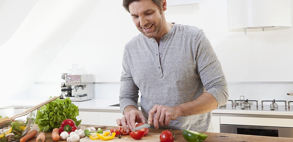 Homme préparant des légumes | Consommez des aliments qui favorisent le sommeil