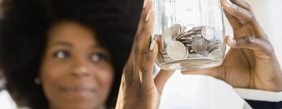 Femme tenant un bocal de monnaie | Suivez la règle des 50/30/20