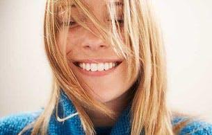 Jeune femme blonde souriant les yeux fermés