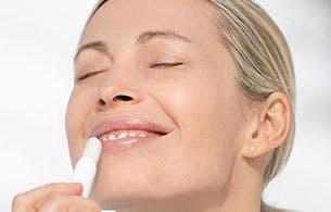 Une jeune femme appliquant un baume pour les lèvres