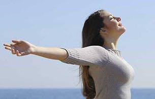 Une femme, les bras en croix, prenant un bol d'air