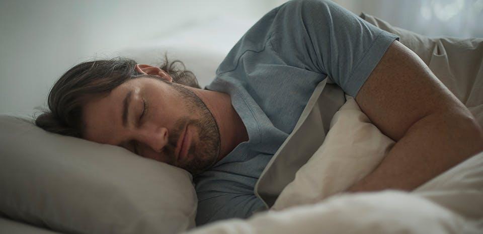 Un homme dormant dans son lit