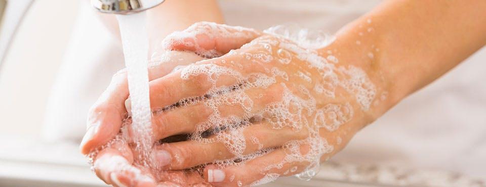 Une personne se lave les mains au lavabo