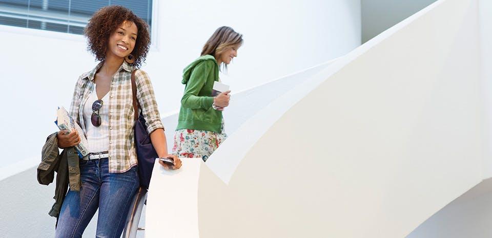Femme souriante dans un escalier | Allez-y à pied