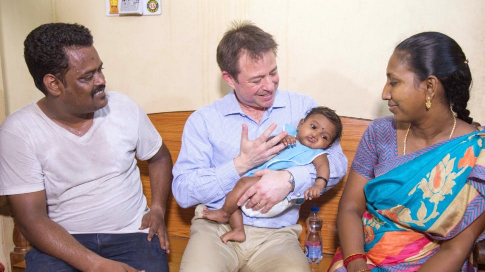 People holding baby with cleft lip.