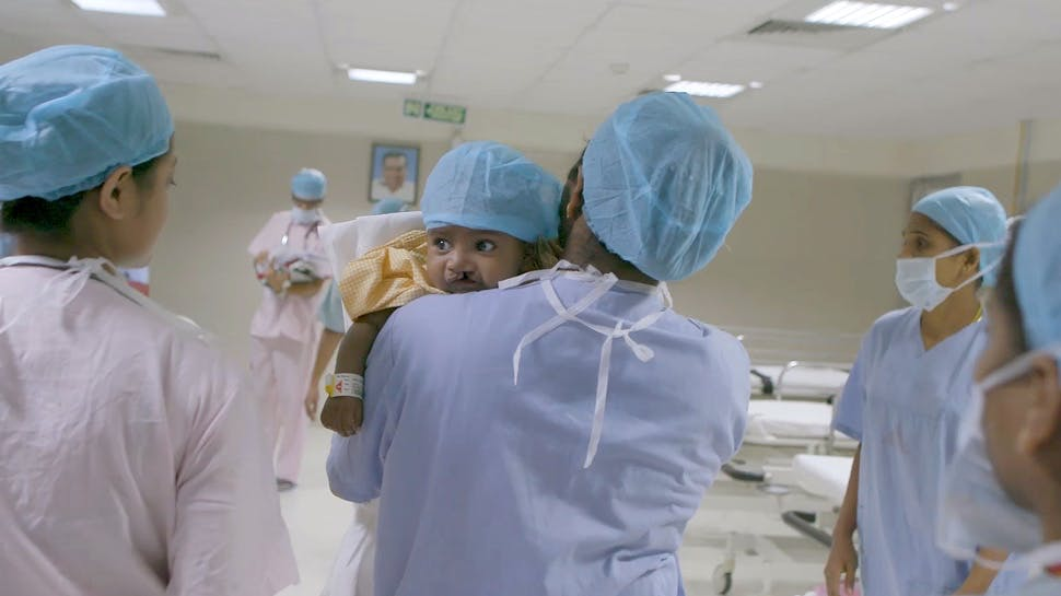 Medical staff holding baby with cleft lip.