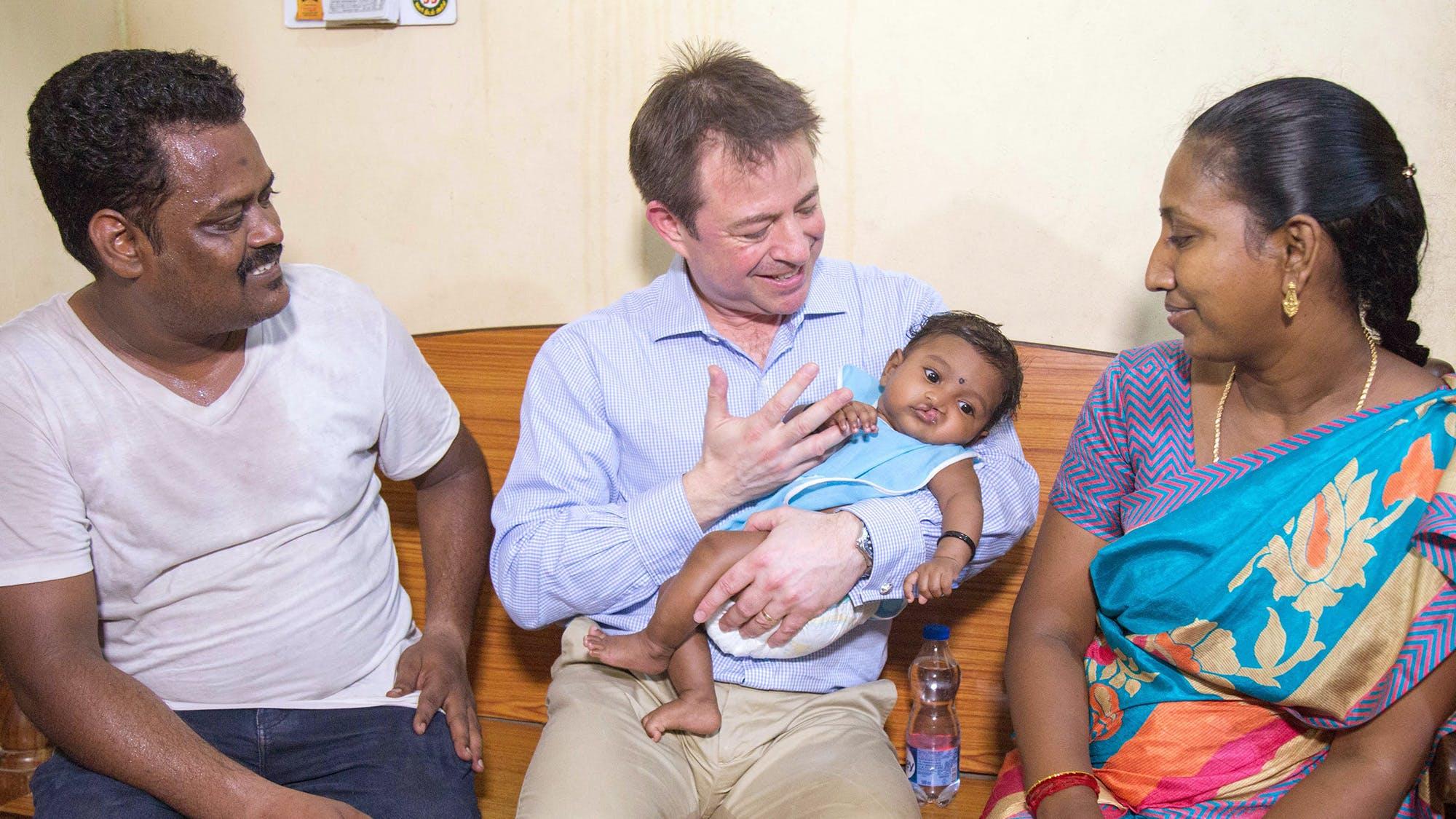 Doctor holds baby sat inbetween parents.