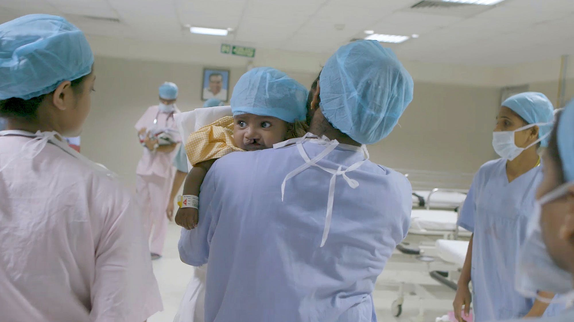 Doctor takes child into surgery.