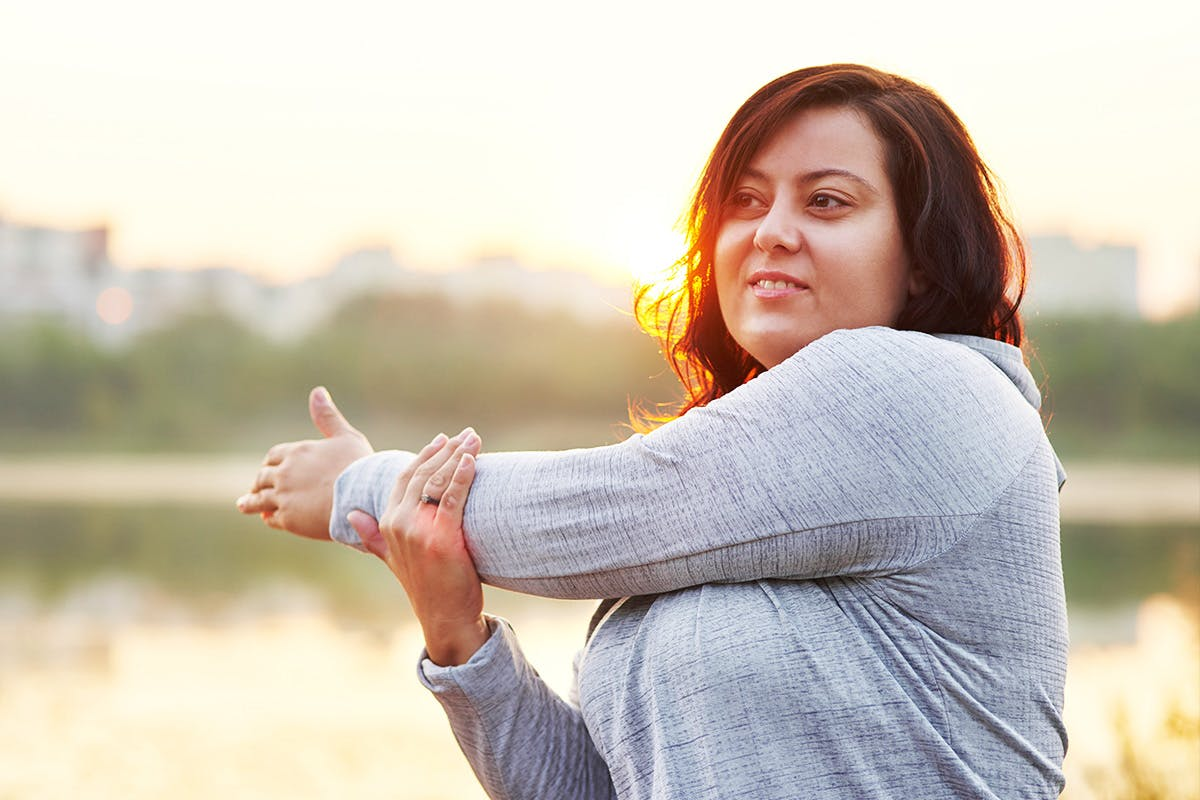 Woman stretching left arm across body