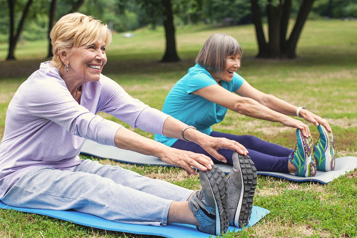 Two women in a seated leg stretch exercise