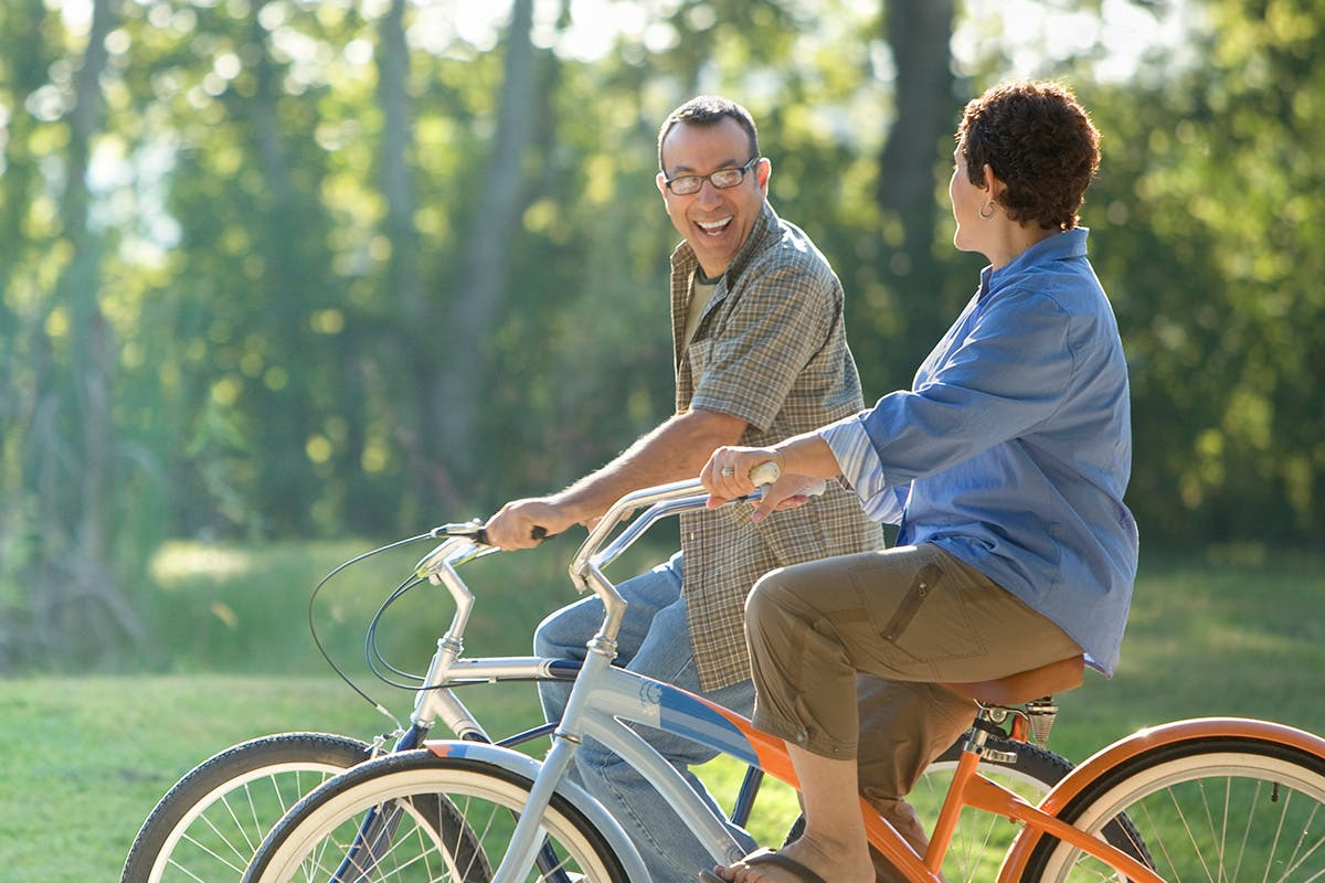 A couple riding their bikes with trees in the background
