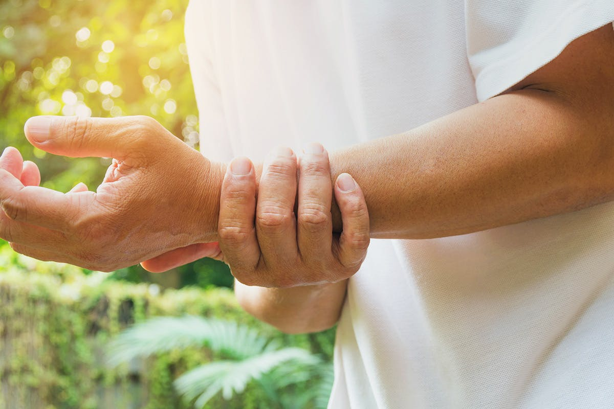 Person holding wrist in pain