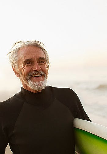 Older man in a wetsuit holding a surfing board