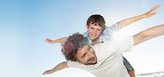 Small boy riding on father's shoulders and pretending to be a plane