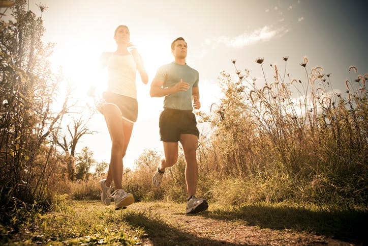 Man and woman jogging together on an outdoor trail.