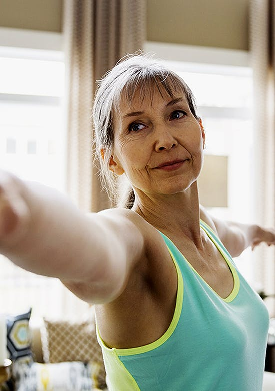 Close-up of middle aged woman stretching her arms