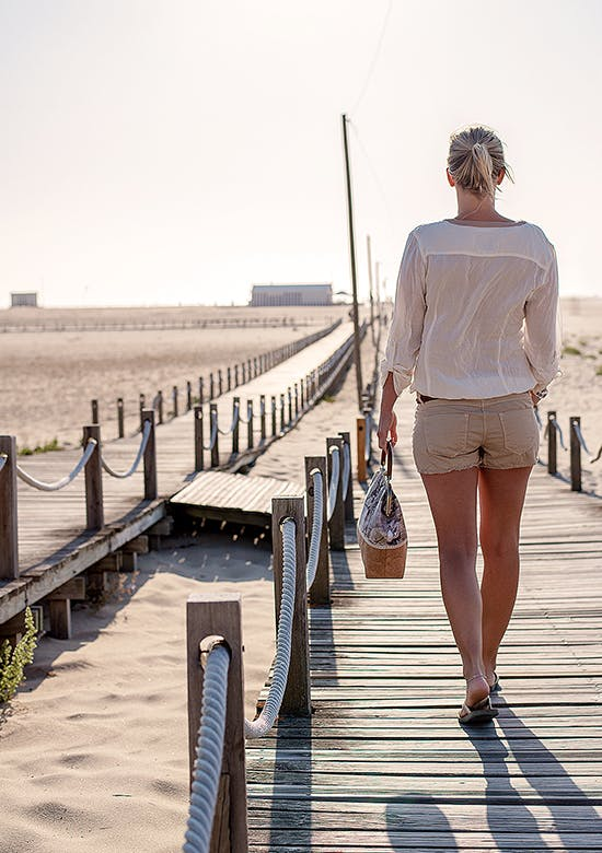 Young woman walking on a beachside boardwalk