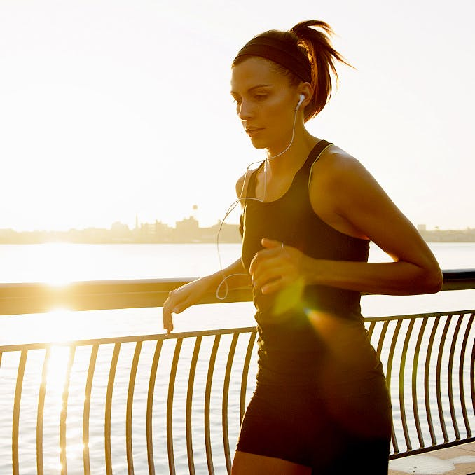 Young woman jogging and listening to music