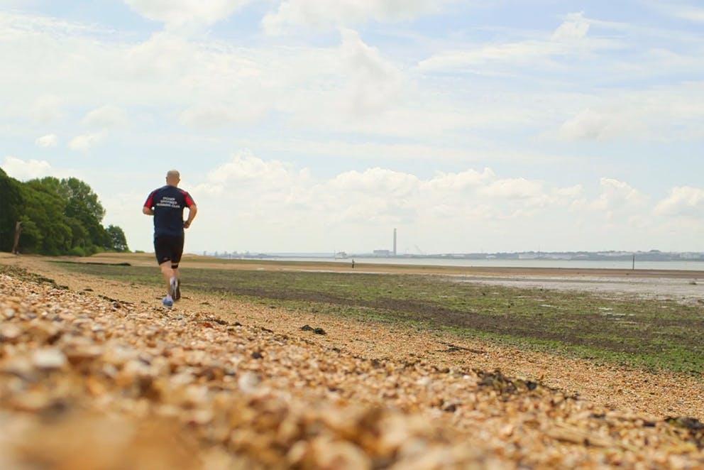 Man jogging down a beach.