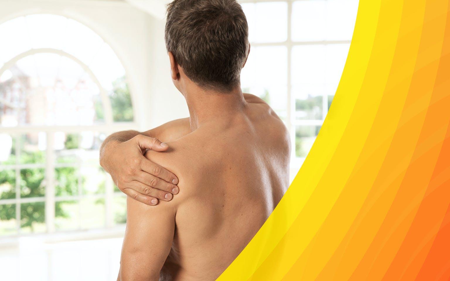 Shirtless man holding his shoulder because of shoulder pain