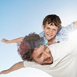 Petit garçon sur les épaules de son père faisant l'avion