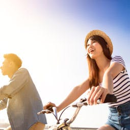 Jeune couple en vélo et souriant