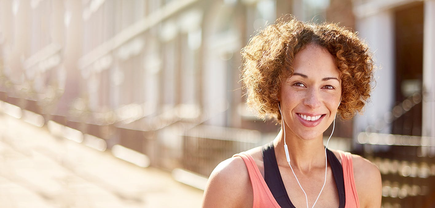 Femme souriante et écoutant de la musique avec des écouteurs