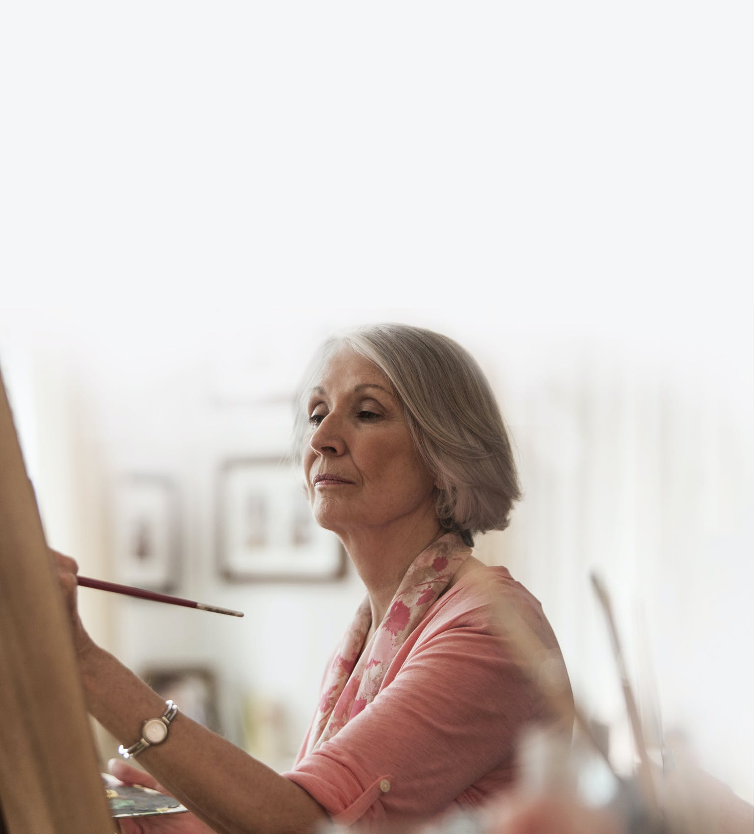 Femme d'âge mûr qui peint une toile sur un chevalet