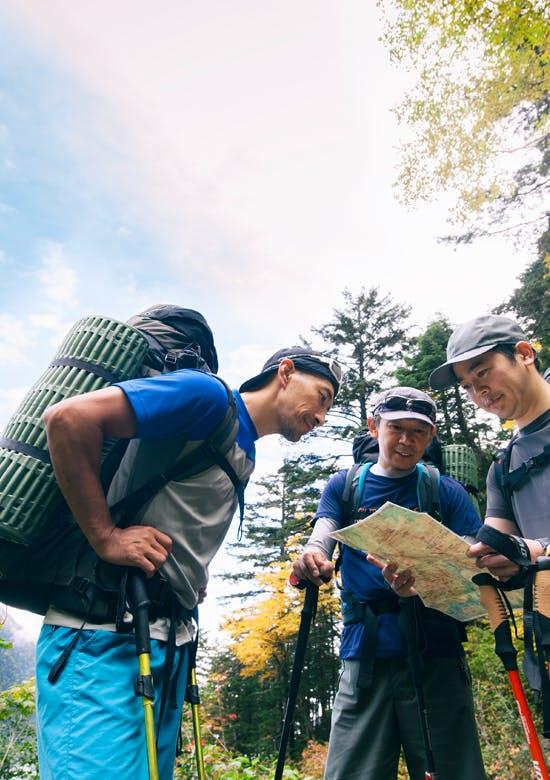 登山中に地図を見る3人の男性