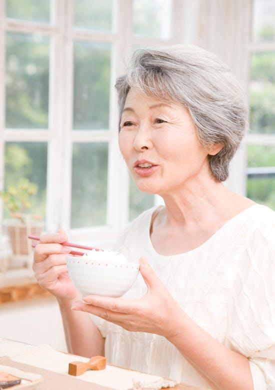 食事をする白髪の女性