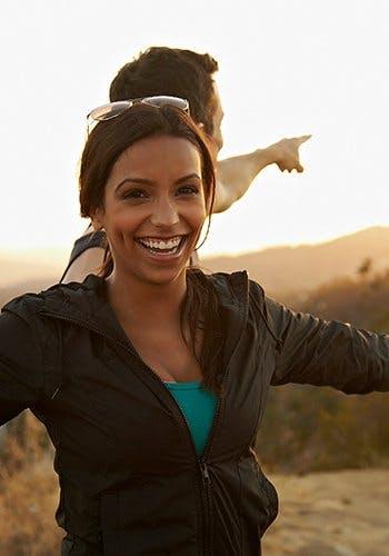 Rodzaje Voltarenu - białoskóry mężczyzna pokazuje na coś w oddali, a ciemnoskóra kobieta uśmiecha się do fotografa