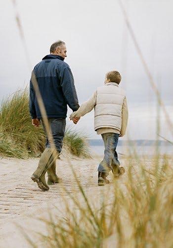Przyczyny bólu - ojciec z synem idą za rękę po plaży