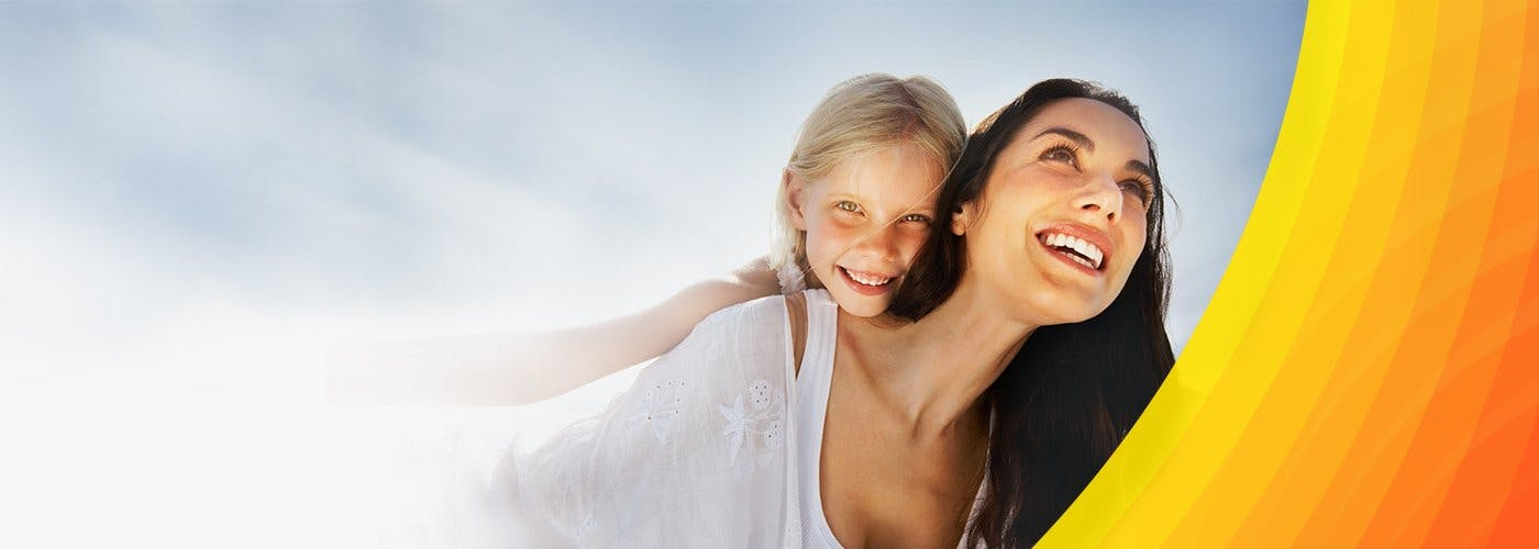 Uśmiechnięta, długowłosa kobieta z zadowolonym dzieckiem