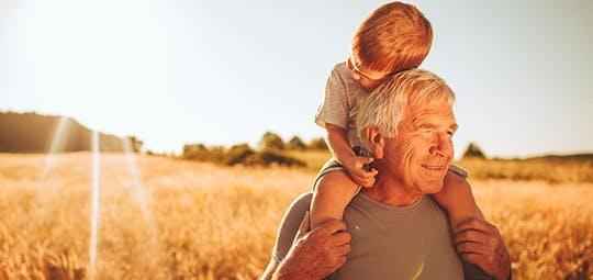 Poznaj swoje ciało i dowiedz jak zmienia się z wiekiem - dziadek niesie wnuczka na barana spacerując po polu.
