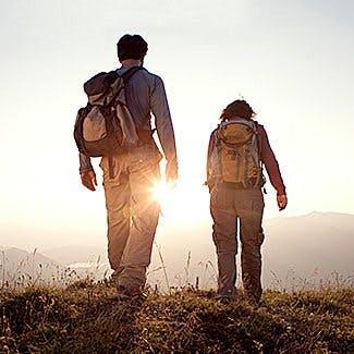 Wszystko co musisz wiedzieć o przeciwdziałaniu bólowi - dwoje ludzi z plecakami na tle zachodzącego słońca