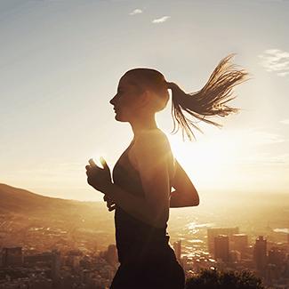 Ćwiczenia i Twoje ciało - biegnąca dziewczyna na tle zachodzącego słońca