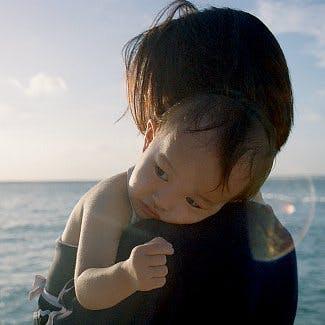 Małe dziecko na ramionach swojej mamy na tle morza